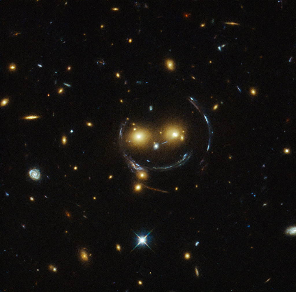 The galaxy cluster SDSS J1038+4849 (seen as two 'eyes' of the face) bends the light of stars coming from behind them, resulting in the arc of light seen as a 'smile'. The phenomenon is called gravitational lensing and is explained by the general theory of relativity. Credit: gsfc/Flickr, CC BY 2.0
