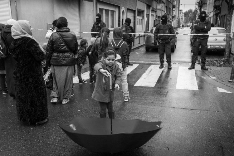 A girl plays with her umbrella in front of masked policemen in the Ransfort street who prevent access to the security perimeter set up during an operation around the Delaunoy street in the predominantly Muslim borough of Molenbeek Saint Jean, in connection with the terrorists attacks in Paris.