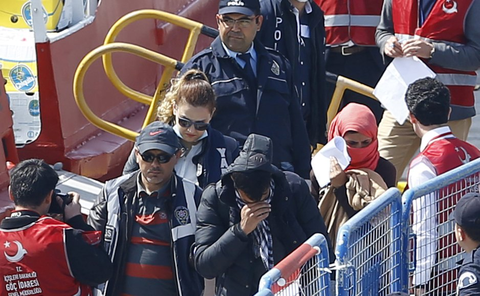 Migrants are escorted by Turkish police officers as they arrive in the Turkish coastal town of Dikili, April 4, 2016. Credit: Reuters/Murad Sezer