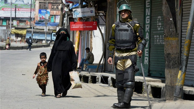 A woman with her child walks past a security jawan in Srinagar during restrictions and a strike following the death of three civilians in firing by security forces during a protest at Handwara in north Kashmir. Credit: PTI