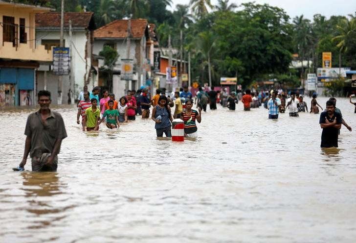 People walk through a flooded road after they moved out from their houses in Biyagama, Sri Lanka. Credit: REUTERS/Dinuka Liyanawatte