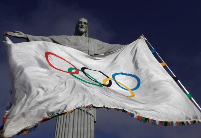 "The Olympic Flag flies in front of ""Christ the Redeemer"" statue during a blessing ceremony in Rio de Janeiro August 19, 2012. Credit: Reuters/Ricardo Moraes"