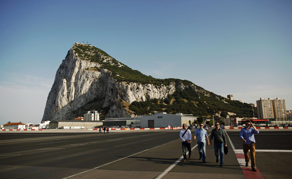 Pedestrians leave the British colony of Gibraltar to Spain, crossing a road at the airport, in Gibraltar. credit: Reuters/Jon Nazca/Files