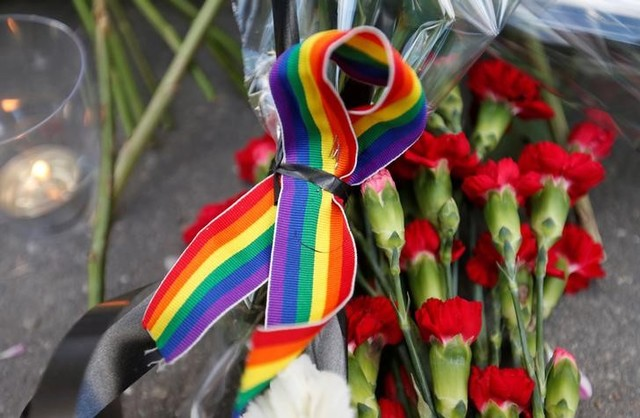 A rainbow ribbon, a candle and flowers for the victims of the shooting at a gay nightclub in Orlando are seen in front of the US Embassy in Moscow, Russia, June 13, 2016. Credit: Reuters/Maxim Zmeyev