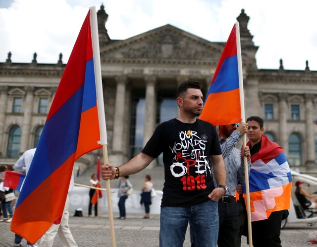 "Supporters holds Armenian flags in front of the Reichstag, the seat of the lower house of parliament Bundestag in Berlin, Germany, June 2, 2016, as they protest in favour of approval of a symbolic resolution by Germany's parliament that declares the 1915 massacre of Armenians by Ottoman forces a ""genocide"". Credit: Reuters/Hannibal Hanschke"