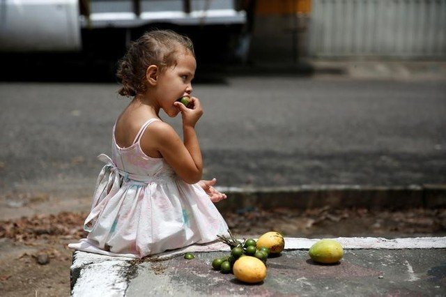 """A girl eats a tropical fruit called """"Mamon"""" while seated next to some mangoes on a street in La Fria, Venezuela, June 2, 2016. Credit: Reuters/Carlos Garcia Rawlins"""