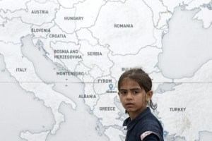 A girl walks past a map illustrating part of Europe, at a makeshift camp for refugees and migrants at the Greek-Macedonian border near the village of Idomeni, Greece, May 19. Credit: Reuters/Kostas Tsironis/Files
