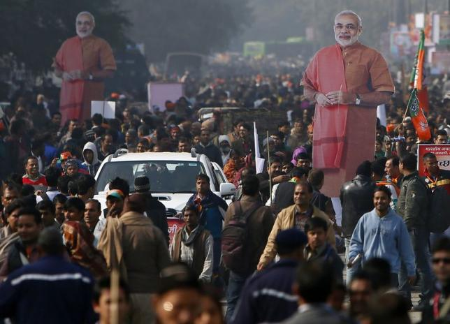 Supporters carry giant cut-outs of Indian Prime Minister Narendra Modi after attending a campaign rally that was addressed by Modi ahead of state assembly elections, at Ramlila ground in New Delhi January 10, 2015. Credit: Reuters/Anindito Mukherjee