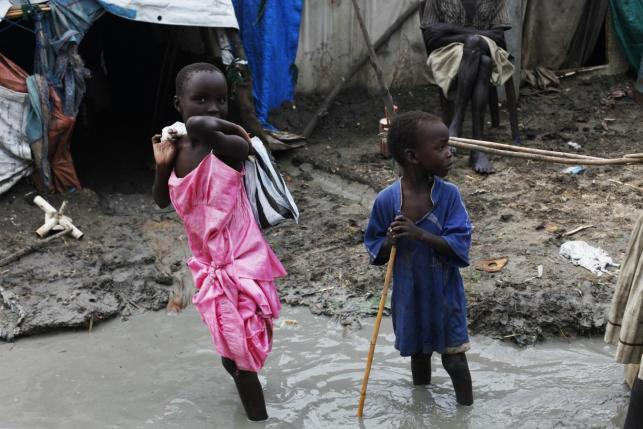 Children walk through mud in the internally displaced persons (IDP) camp inside the United Nations base in Malakal July 23, 2014. Credit: Reuters/Andreea Campeanu