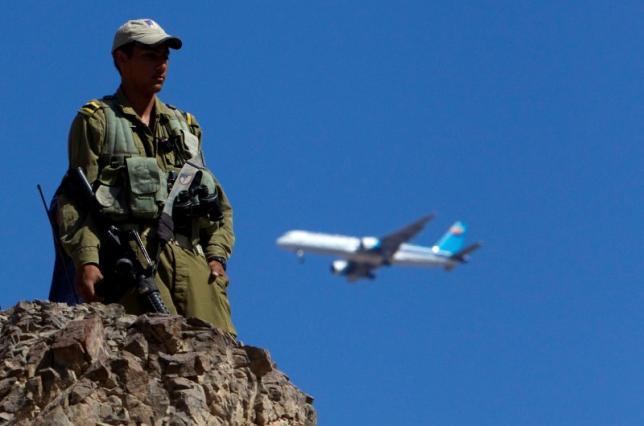 A plane flies overhead as an Israeli soldier stands guard near the Israeli-Egyptian border August 19, 2011. Credit: Reuters/Ronen Zvulun