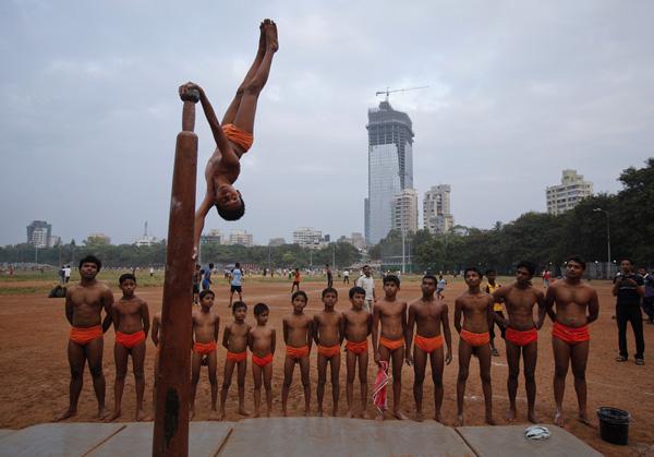 A boy performs a Mallakhamb pose on a pole as others watch at the Shree Samartha Vyayam Mandir in Mumbai, October 21, 2012. Credit: Reuters/Vivek Prakash