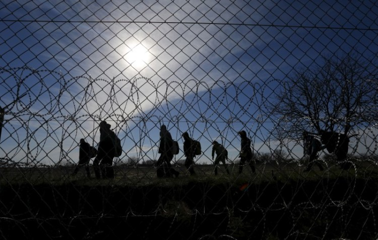 Migrants walk along Hungary's border fence on the Serbian side of the border near Morahalom, Hungary, February 22, 2016. Credit: Reuters/Laszlo Balogh