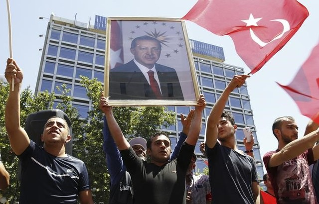 Supporters of Tukish President Tayyip Erdogan lift up his portrait as they celebrate with flags in Ankara, Turkey, July 16, 2016. REUTERS/Tumay Berkin