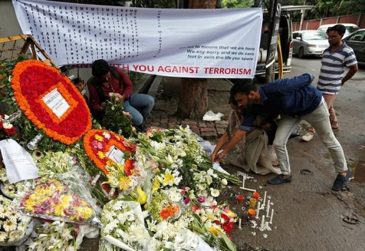 People place flowers at a makeshift memorial near the site, to pay tribute to the victims of the attack on the Holey Artisan Bakery and the O'Kitchen Restaurant, in Dhaka, Bangladesh, July 5, 2016. Credit: Reuters