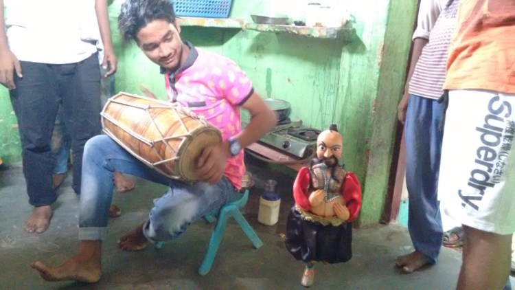 A puppeteer of Kathputli Colony playing his drum, with a puppet in the background. Credit: Jahnavi Visvanathan