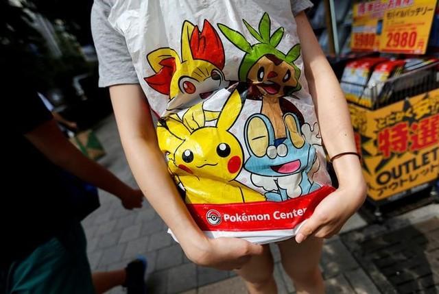A woman holds a shopping bag of Pokemon in Tokyo's Akihabara district, Japan July 20, 2016. Credit: Reuters/Toru Hanai