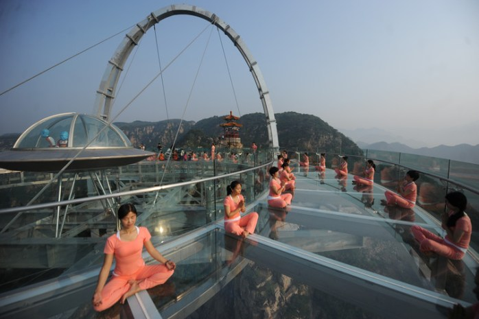 People practise yoga at a glass sightseeing platform ahead of the International Day of Yoga, on the outskirts of Beijing. Credit: Reuters