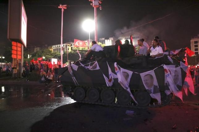 Supporters of Turkish President Tayyip Erdogan sit atop an armored vehicle decorated with Erdogan's portraits in Ankara, Turkey July 16, 2016. Credit: Reuters/Tumay Berkin