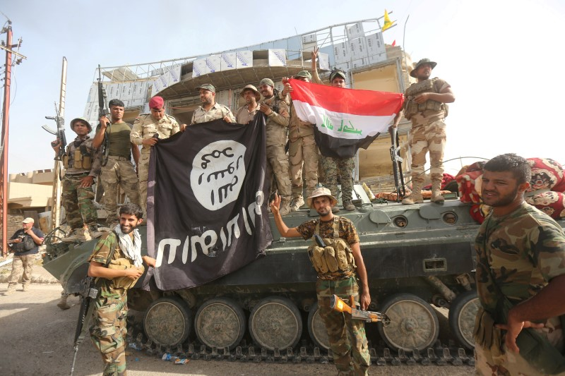 Shi'ite fighters and Iraqi security forces hold an Islamic State flag (L), which they pulled down after clashes with IS militants, in Saqlawiya, north of Falluja, Iraq, June 4, 2016. Credit: REUTERS/Stringer/Files