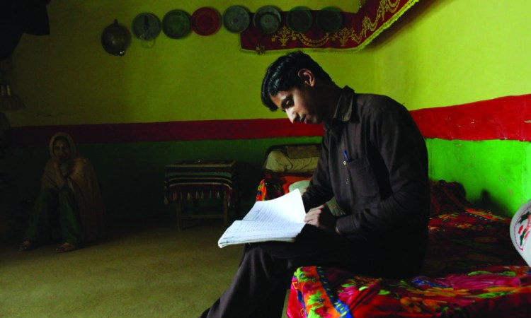 Ambreen's brother Nauman looks through his notebook at his house in Makol. Credit: Annie Ali Khan/The Herald