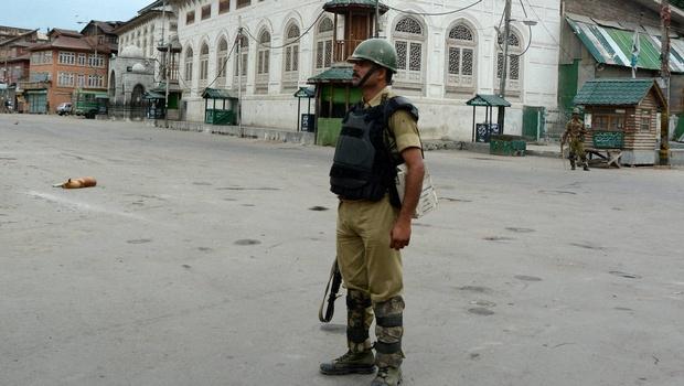 A security Jawan stands guard during curfew in Srinagar. Credit: PTI
