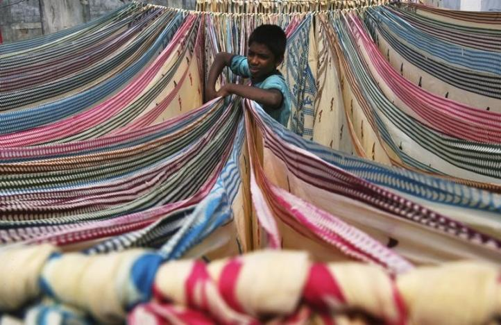 A boy separates starched sarees left to dry on the roof of a cotton factory in Hyderabad. Credit: Reuters/Krishnendu Halder/Files