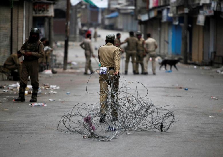 A policeman pulls concertina wire to lay a barricade on a road in Srinagar. Credit: Reuters/Danish Ismail