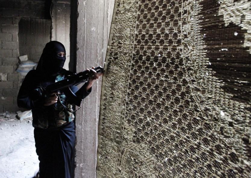 Um Radwan, a female fighter in the Free Syrian Army, looks through a curtain in Aleppo's Bustan al-Basha district, October 3, 2013. Credit: Muzaffar Salman/ Reuters