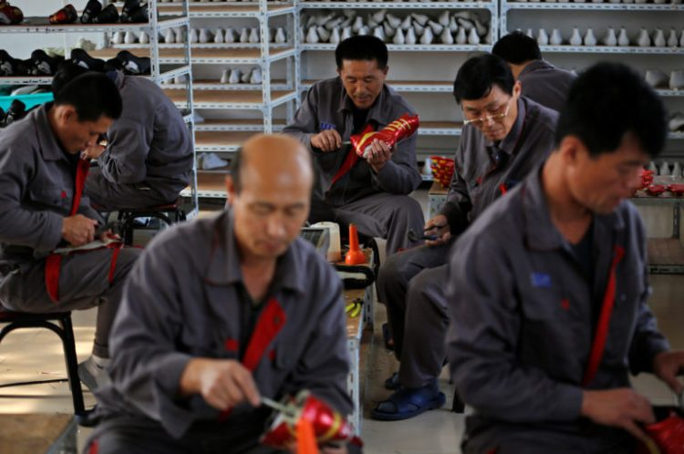 North Korean workers make soccer shoes inside a temporary factory at a rural village on the edge of Dandong October 24, 2012. Credit: Aly Song/Reuters/Files