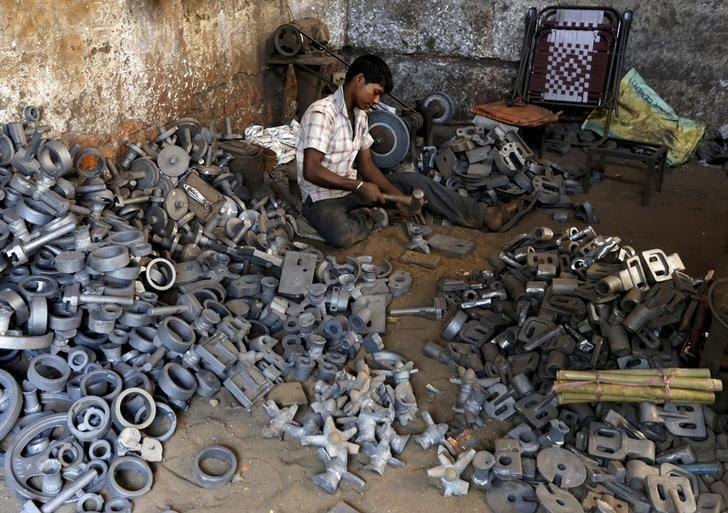 A worker separates casting joints of gearboxes inside a small-scale automobile manufacturing unit in Ahmedabad, India, October 12, 2015. Credit: Reuters/Amit Dave/File Photo