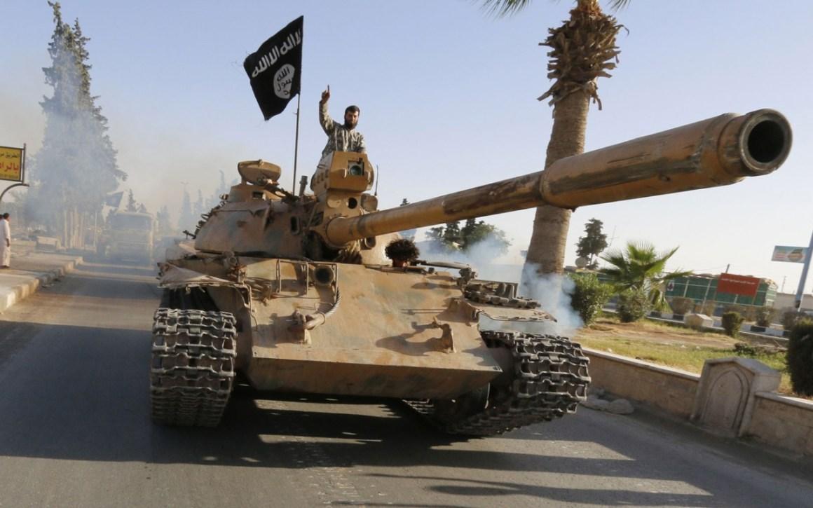 An ISIS militant flies the black flag in Raqqa, Iraq. Credit: Reuters/Files