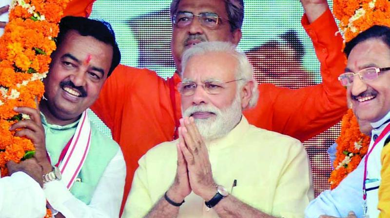 File photo of Prime Minister Narendra Modi (R) being garlanded by UP BJP president Keshav Prasad Maurya (L) and party MP Ramesh Pokhriyal. Credit: PTI