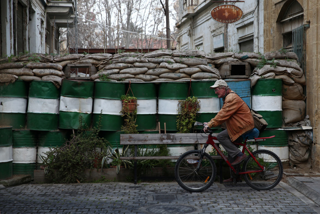 A man rides a bicycle past a barricade outside the UN buffer zone in Nicosia, Cyprus. Credit: Reuters