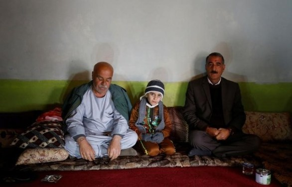Ayman, a boy from a minority Yazidi community, who was sold by ISIS militants to a Muslim couple in Mosul, sits beside his uncle Samir Rasho Khalaf (L) after he was returned to his Yazidi family in Duhok, Iraq, January 31, 2017. Credit: Reuters
