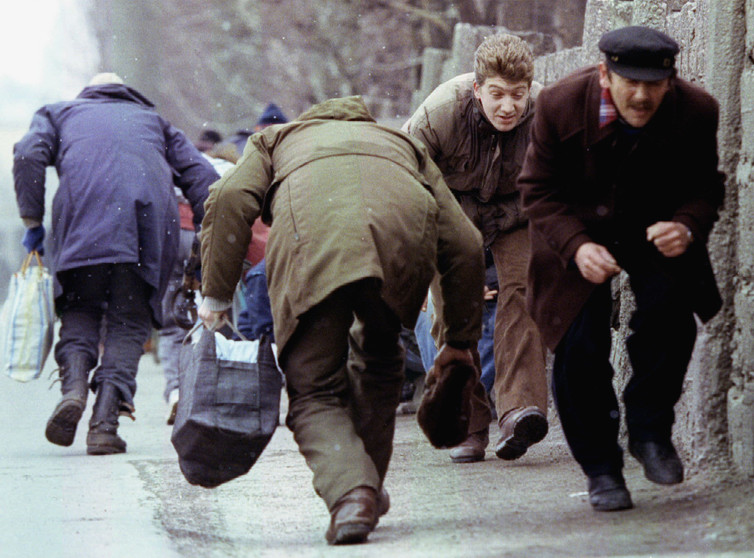 People run for cover as they pass an area of heavy Serb sniper fire in the besieged Sarajevo, Bosnia, 1993. Credit: Reuters/Chris Helgren