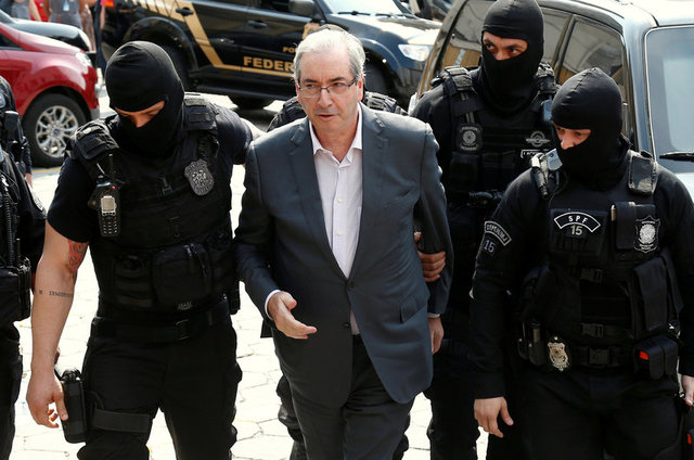 Former speaker of Brazil's Lower House of congress, Eduardo Cunha (C), is escorted by federal police officers as he arrives to the Institute of Forensic Science in Curitiba, Brazil, October 20, 2016. Credit: Reuters
