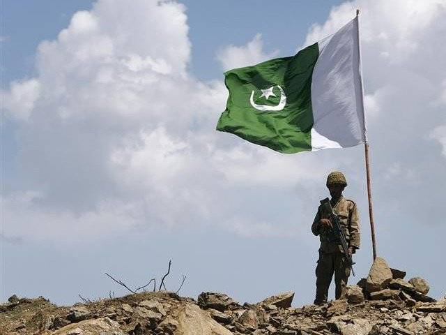 A soldier standing next to a Pakistani flag. Credit: Reuters/Files