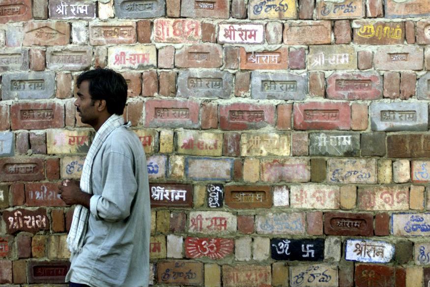 A Hindu activist walks past a temple wall, where devotees have written the name of Ram, in Ayodhya October 18, 2003. Credit: Reuters/Roy Madhur