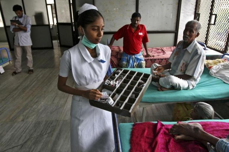 A paramedic distributes free medicine provided by the government to patients inside a ward at Rajiv Gandhi Government General Hospital (RGGGH) in Chennai July 12, 2012. REUTERS/Babu/Files