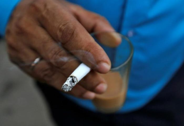 A man smokes a cigarette along a road in Mumbai, October 26, 2016.Credit: Reuters