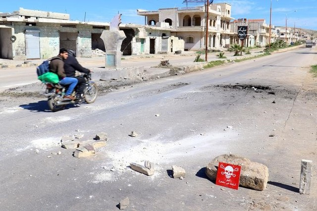 """Men ride a motorbike past a hazard sign at a site hit by an airstrike on Tuesday in the town of Khan Sheikhoun in rebel-held Idlib, Syria April 5, 2017. The hazard sign reads, """"Danger, unexploded ammunition"""". Credit: Reuters"""