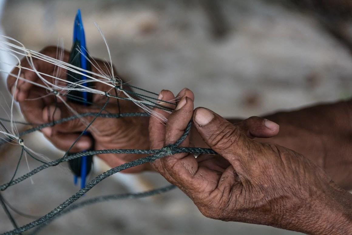 Mr Kamaruddin, 70, is fixing his net on the beach next to his home at Tanjung Tokong, Penang Island. Credit: Rod Harbinson via Mongabay