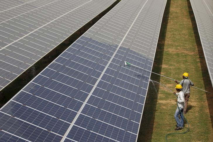 Workers clean photovoltaic panels inside a solar power plant in Gujarat, India, in this July 2, 2015 file photo. Credit: Reuters/Amit Dave/Files