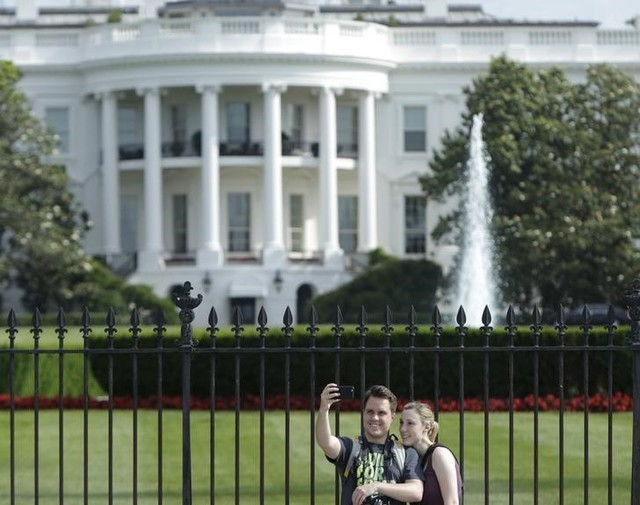 Tourists take selfies by the original South Lawn security fencing at the White House in Washington May 28, 2015. Credit: Reuters /Gary Cameron