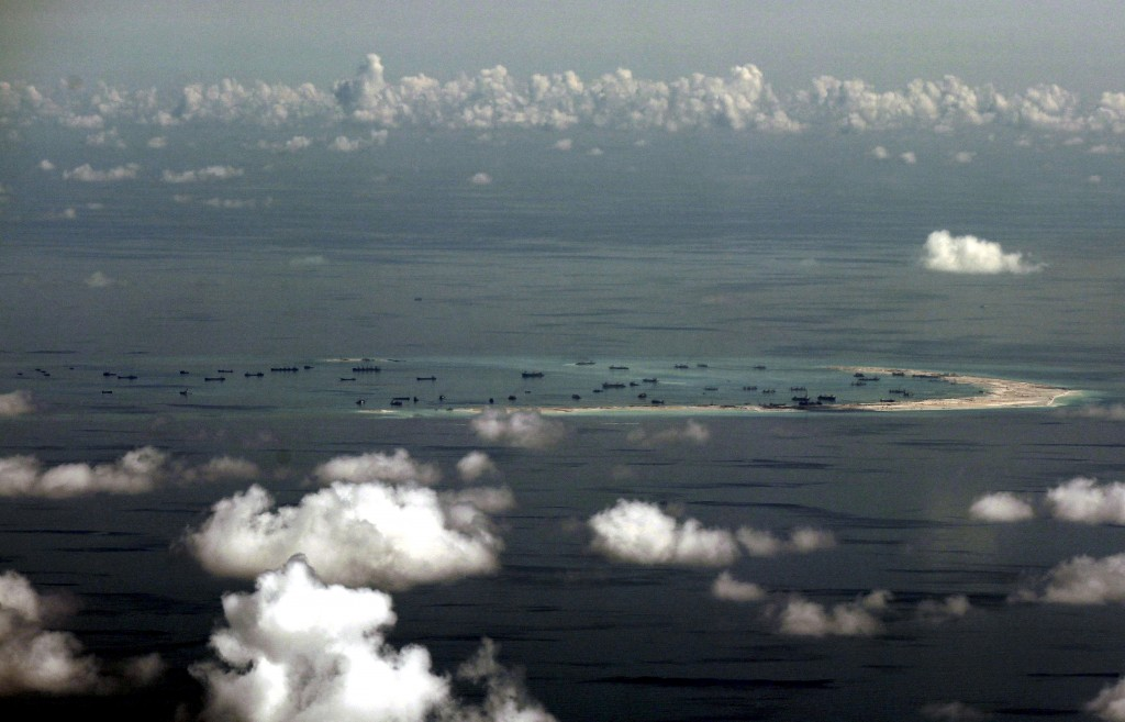 An aerial photo taken though a glass window of a Philippine military plane shows the alleged on-going land reclamation by China on mischief reef in the Spratly Islands in the South China Sea, west of Palawan, Philippines, May 11, 2015. Credit: Reuters/Files