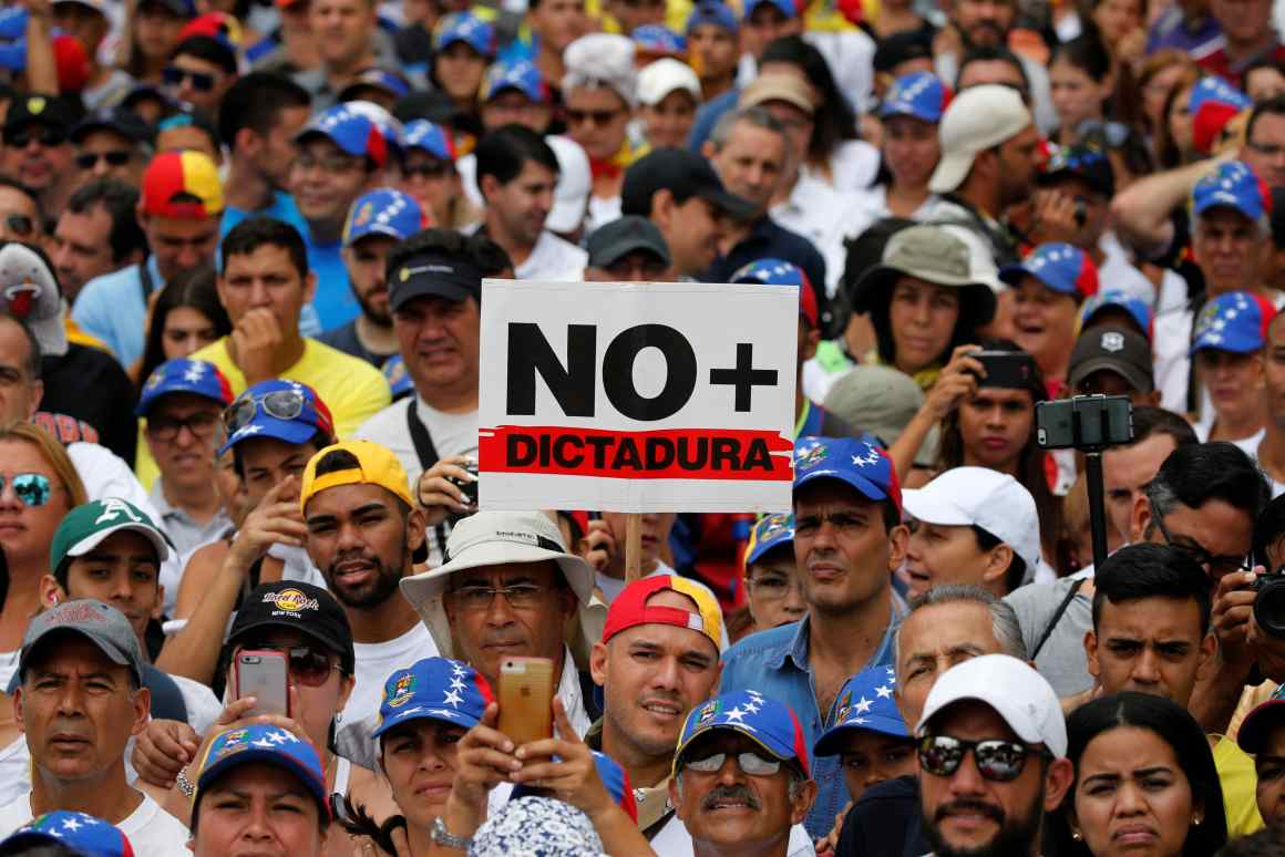 Demonstrators hold placard that reads: 'No more dictatorship' while rallying against Venezuela's President Nicolas Maduro in Caracas, Venezuela May 1, 2017. Credit: Reuters/Carlos Garcia Rawlins