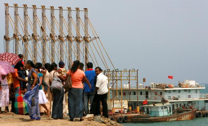 A group of Sri Lankan visitors at the new deep water shipping port watch Chinese dredging ships work in Hambantota, 240 km (150 miles) southeast of Colombo, March 24, 2010. Credit: Reuters/Andrew Caballero-Reynolds/Files