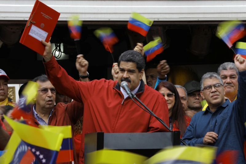 """Venezuela's President Nicolas Maduro holds a document with the details of a """"constituent assembly"""" to reform the constitution during a rally at Miraflores Palace in Caracas, Venezuela May 23, 2017. Credit: Reuters/Carlos Barria"""