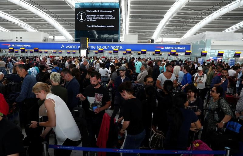 People wait with their luggage at the British Airways check in desks at Heathrow Terminal 5 in London, Britain May 28, 2017. Credit: Reuters/Neil Hall