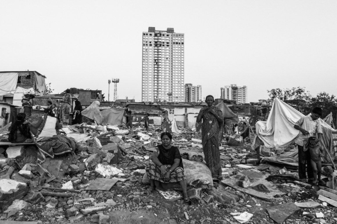Residents sit amidst their demolished homes. Credit: Javed Iqbal